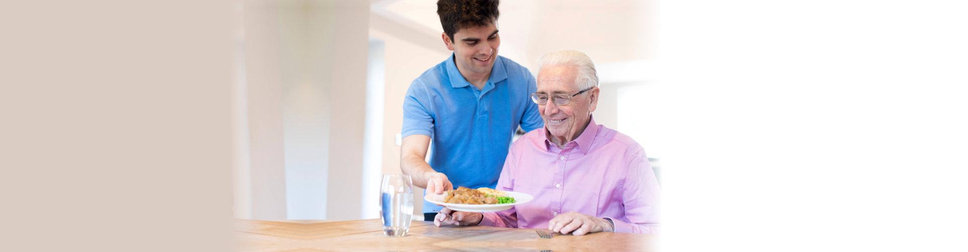 caregiver serving elder man a meal